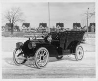 1908 Packard 30 Model UA touring car with houses in background on winter street