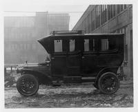 1908 Packard 30 Model UA by factory, two brick buildings in background