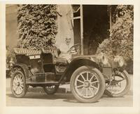 1910 Packard 18, parked on street with male driver