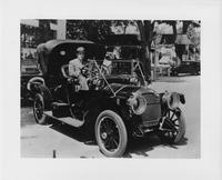 1910 Packard 30 Model UC with male driver, front view, parked on street