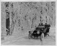 1912 Packard phaeton, on winter road, with male driver and two passengers