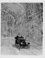 1912 Packard phaeton, on winter road, with male driver and two passengers, front view
