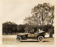 1912 Packard with top folded, two males in front & two females in back