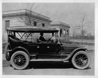 1916 Packard 1-25 touring car with long mileage record, parked in front of large stone building