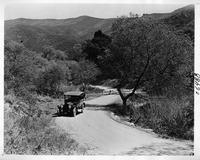 1917 Packard on country road with top raised and mountains in background