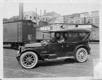 1917 Packard touring car in rail yard, several buildings in background