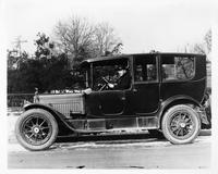 1917 Packard limousine with male chauffeur, parked on street, left side view