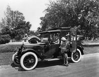 1918 Packard landaulet, parked on street, male driver, two female passengers, one female standing next to car