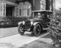 1918-1919 Packard limousine, parked in driveway with male chauffeur, next to large brick home
