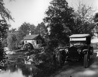 1920 Packard phaeton, parked on country road by stream and mill