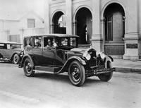 1920 Packard on street, female driver, in front of stone building