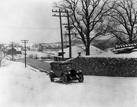 1920-1921 Packard touring car driving up a snowy hill by stone wall