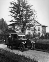 1921-1922 Packard touring car with female driver next to large house