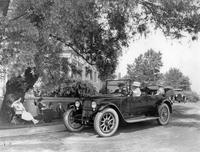 1920-1923 Packard phaeton, on residential street next to group of people under a tree