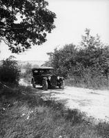 1920-1923 Packard touring car, on country road with male driver, top raised