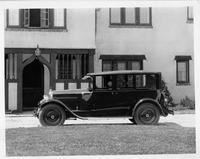 1925 Packard sedan, left side view, male chauffeur, parked in front of large home