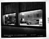 1925 Packards in dealership showroom, through window at night