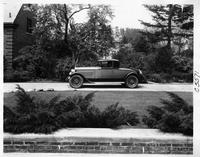 1926 Packard two-toned coupe, left side view, parked in driveway, female driver