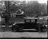 1927 Packard coupe, left side view, parked on street, garden in background