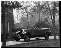 1927 Packard phaeton, three-quarter right front view, top lowered, male behind wheel