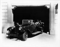 1928 Packard touring car leaving with female driver and passengers