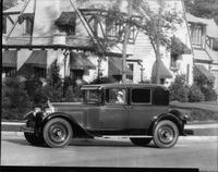 1928 Packard club sedan, parked on residential street, female driver at wheel