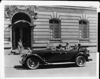 1928 Packard touring car parked on street with male chauffeur