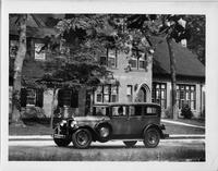1928 Packard sedan, seven-eights left front view, on residential street, male behind wheel