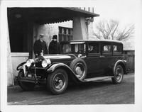 1928 Packard sedan limousine parked in front of house, couple standing at passenger side