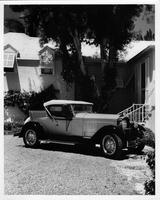 1929 Packard runabout, seven-eights left front view, top raised, parked in driveway, house in background