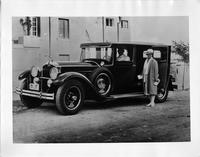 1929 Packard sedan limousine, male chauffeur, female standing at passenger door