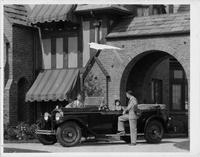 1929 Packard phaeton at entrance to large brick home, female at wheel