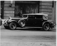 1929 Packard convertible sedan, nine-tenths left front view, top raised, parked on street