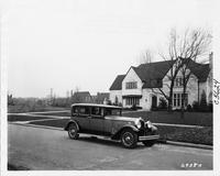 1930 Packard sedan parked on street in front of large home