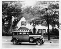 1930 Packard sedan, right side view, parked on street, in front of house