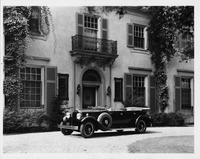 1930 Packard touring car, three-quarter left side view, top folded, parked on drive in front of house