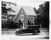 1930 Packard sedan limousine, left side view, parked on street in front of large brick home