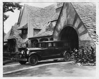 1930 Packard sedan limousine,  three-quarter left side view, parked on drive at side of large brick home