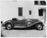 1930 Packard roadster, right side view, top folded, parked by building