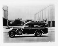 1930 Packard special funeral coach, left side view, male driver, parked on street