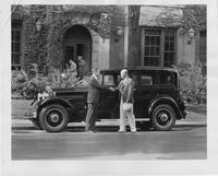 1931 Packard sedan, left side view, parked on street, two men shaking hands at side of car