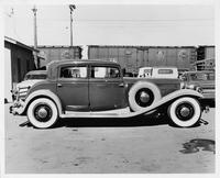 1931 Packard sedan, right side view, other cars and train in background
