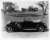 1931 Packard convertible victoria, left side view, top folded, in park setting