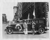 1932 Packard sedan, left side view, parked on city street, two men standing at side