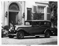 1932 Packard sedan parked on drive in front of house, women at doorway