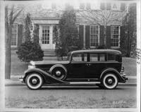 1933 Packard sedan, left side view, parked on street in front of house