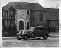 1933 Packard sedan, three-quarter left side view, parked on drive in front of large brick house