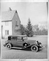 1933 Packard club sedan, parked on drive next to stone house