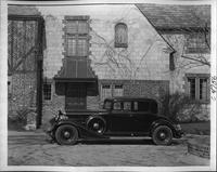 1933 Packard coupe, left side view, parked on driveway in front of large brick house