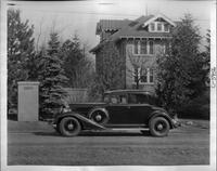 1933 Packard coupe, left side view, parked on street, brick house in background
